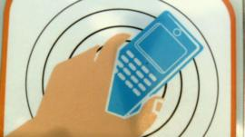 A NFC tag showing a hand holding a mobile phone
