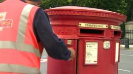 Postman collects letters from a post box