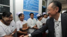 Jim Yong Kim, president of the World Bank Group, shakse hands with a nurse as he arrives at a township hospital on the outskirts of Yangon