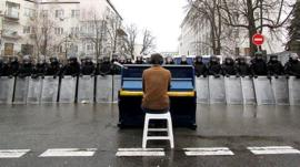 Man playing piano in front of a line of riot police