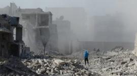 Man stands amid rubble in Aleppo