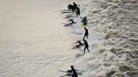 Surfers ride Severn Bore