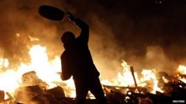 Protester throwing tyre at fire
