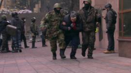 An injured protester is taken away in Kiev