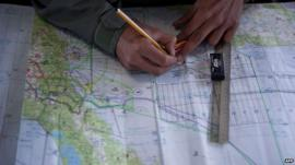 Royal Malaysian Air Force Navigator captain marks locations on a map