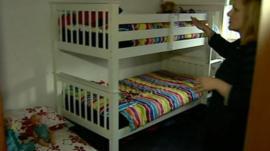 Women in bedroom with three beds