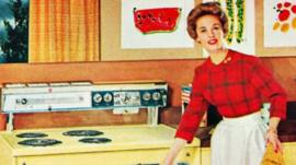 Woman standing by a stove