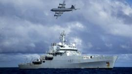 HMS Echo, as a Lockheed P-3 Orion flies overhead, in the southern Indian Ocean