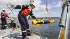 A submarine built by Bluefin Robotics is lowered into the water by systems engineer Cheryl Mierzwa in Quincy