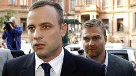 Olympic and Paralympic track star Oscar Pistorius (L) arrives ahead of his trial at North Gauteng High Court in Pretoria April 15, 2014