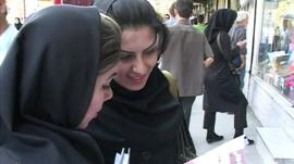 Two Iranian women wearing headscarves, but showing their hair in the street