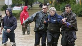 Members of the Bosnian army rescue a woman stranded in her home due to flooding in the Bosnian town of Maglaj