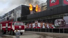 A boy walks by as firefighters attempt to extinguish a fire at the sports arena Druzhba , which is the home venue of the ice hockey club