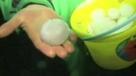 Hand holds bucket of giant hail stones in Wilber, Nebraska