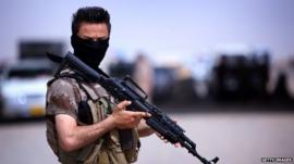 A masked Pershmerga fighter from Iraq's autonomous Kurdish region guards a temporary camp