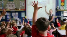 Children with their hands up in a school classroom