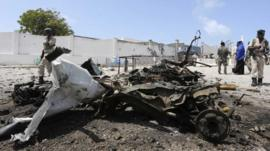 Somali government soldiers gather near the wreckage after a suicide car explosion near the Somali parliament building in Mogadishu