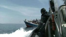 Archive footage of officials approaching boat of asylum seekers