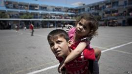 Displaced Palestinian children stand on the yard of an United Nations (UN) school in Jabalia in the northern Gaza Strip