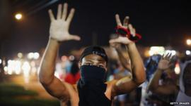 A demonstrator confronts police during a protest over the shooting of Michael Williams