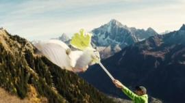 The wingsuit pilot 'high fives' the hand-on-a-stick