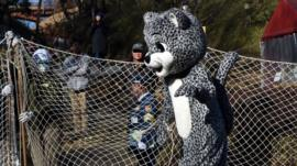 A keeper dressed as a snow leopard