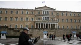 A man and a pigeon stand outside the Greek parliament
