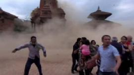 Still from footage of people running as temple collapses
