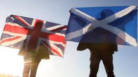 Scottish and English flags held up over Edinburgh, Scotland