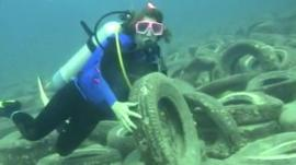 Diver holds up tyre under water