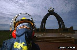Worker in front of The Billionth Barrel of Oil Monument, Seria, Brunei