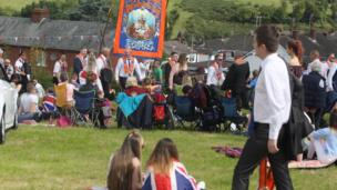Spectators sitting on seats watching the parade congregate in a field in Richhill, Armagh, 12 July 2017