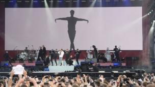 المغنية الأمريكية أريانا غراندي برفقة موسيقيين في فرقتها يحيون الحفل الغنائي لصالح أقارب ضحايا هجوم مانشستر.
