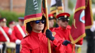 A flag is draped over uniformed band member's head as he marches in a parade