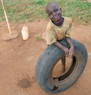 A boy smiles with a tyre