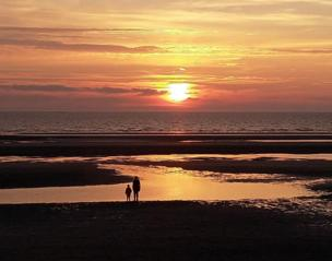 An adult and a child stand on a beach looking at the sea as the sun sets