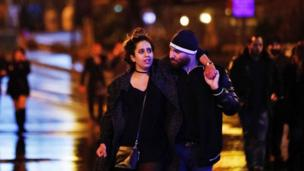 Young people leave from the scene of an attack in Istanbul, early Sunday, Jan. 1, 2017