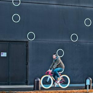 Man cycling past circles