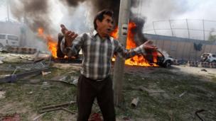 ชายคนหนึ่งยืนอยู่เบื้องหน้ารถยนต์ที่เกิดเพลิงลุกไหม้