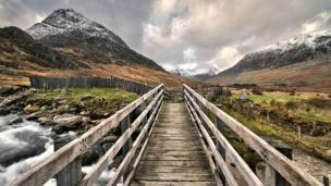 This view of a bridge over Nant Gwern y Gof river with Tryfan mountain in the distance.