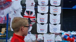Twelfth of July merchandise stall with boy walking past