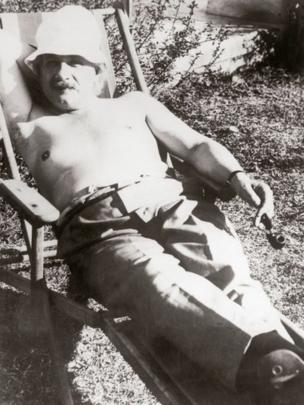 Einstein relajado con el dorso al descubierto y fumando su pipa.