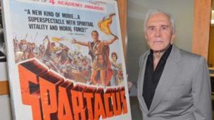 كيرك دوغلاس بجوار ملصق دعائي لفيلم سبارتاكوس