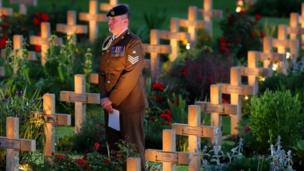 Soldier standing among the crosses of the missing