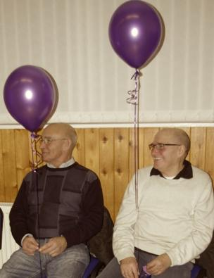 Two granddads' hold purple balloons as they sit and smile
