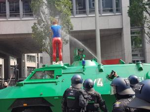 Police use spray against a protester standing on an armoured car in Hamburg, 7 July