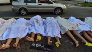 مجموعة من النساء في بنما يقدمن مشهدا تمثيلية بملاءات بيضاء مغطاة بدماء مزيفة لإحياء ذكرى نساء قتلن بسبب النوع بمناسبة اليوم العالمي للقضاء على العنف ضد المرأة.