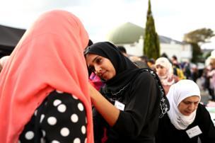 یک زن مسلمان در حال کمک به یکی از شرکتکنندگان برای گذاشتن حجاب در شهر اوکلند در مراسم یادبود کشتهشدگان کرایستچرچ، نیوزیلند