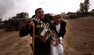 أحد أفراد الفرقة الذهبية يحمل مسنّا إلى مكان آمن لحمايته خلال معركة في منطقة طوبزاوه