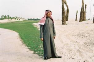 A man stands by a sandy road on a golf course
